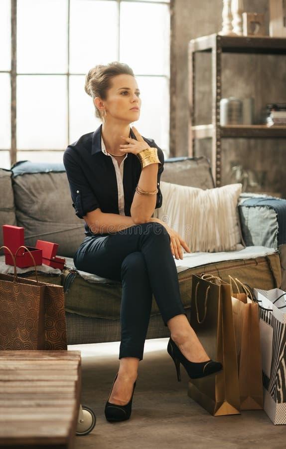 Mujer rica que se sienta en el sofá entre los panieres en desván foto de archivo
