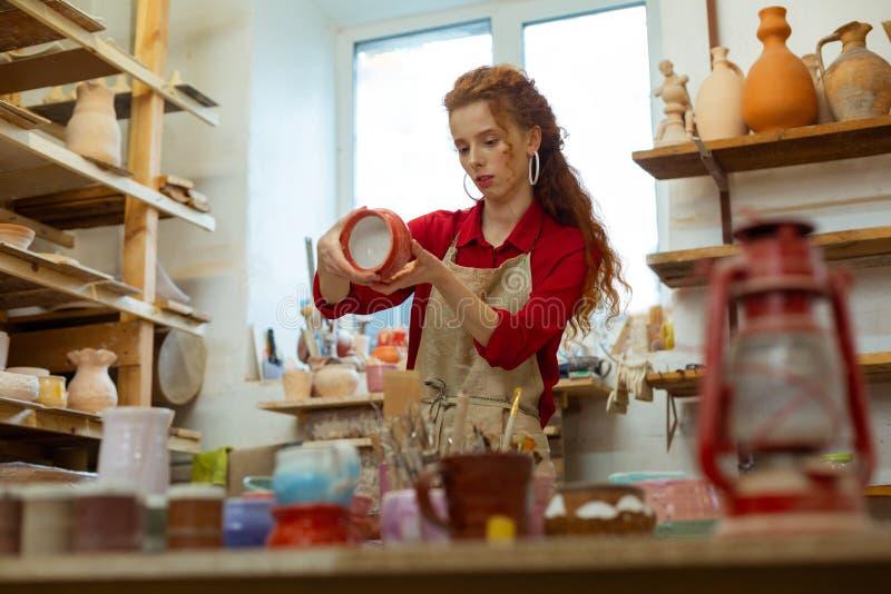 Mujer rizada apuesta curiosa en camisa roja observando el pote acabado fotografía de archivo
