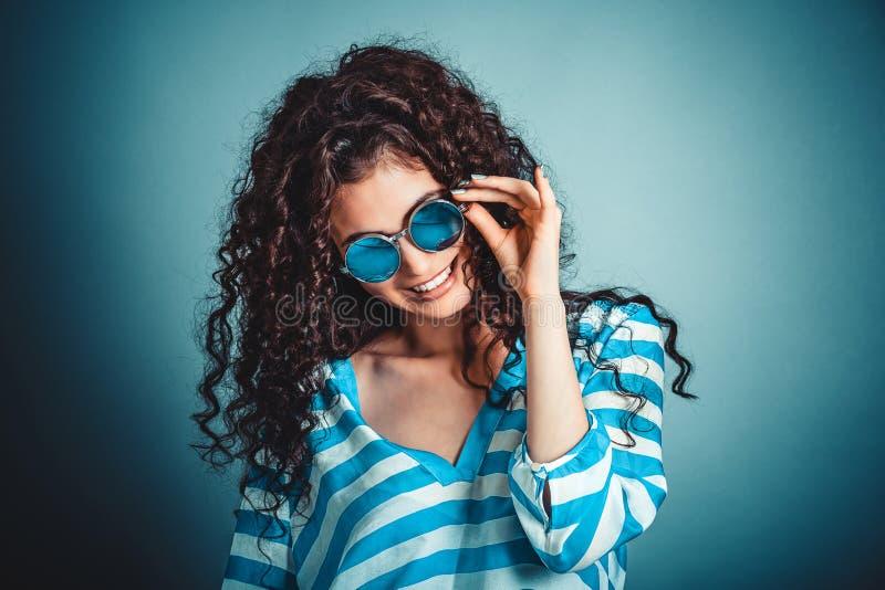 Mujer rizada con las gafas de sol que presentan y que sonríen imagen de archivo libre de regalías