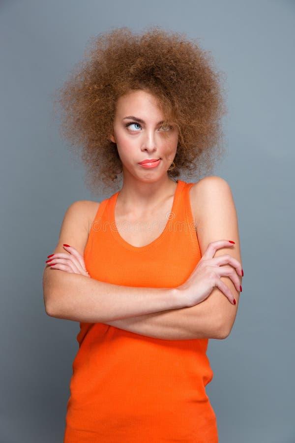 Mujer rizada enfadada aburrida que presenta con los brazos cruzados fotografía de archivo