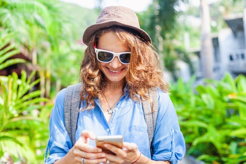Mujer rizada feliz del viajero en sombrero y vidrios con un teléfono en sus manos, en un fondo verde claro de la primavera en la  fotos de archivo