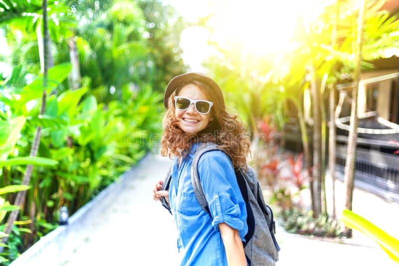 Mujer rizada feliz del viajero en sombrero y vidrios, en fondo verde claro de la primavera en sol fotografía de archivo