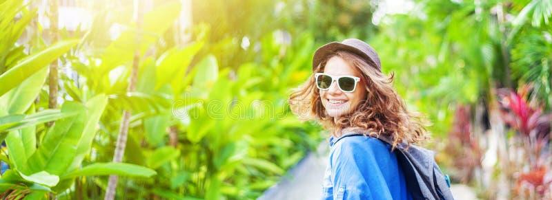 Mujer rizada feliz del viajero en sombrero y vidrios, en fondo verde claro de la primavera en sol imagenes de archivo