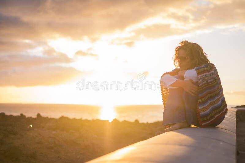 Mujer rizada hermosa que se sienta en una pared y disfrutar de la sensaci?n del tiempo de la puesta del sol la sensaci?n de la li foto de archivo libre de regalías