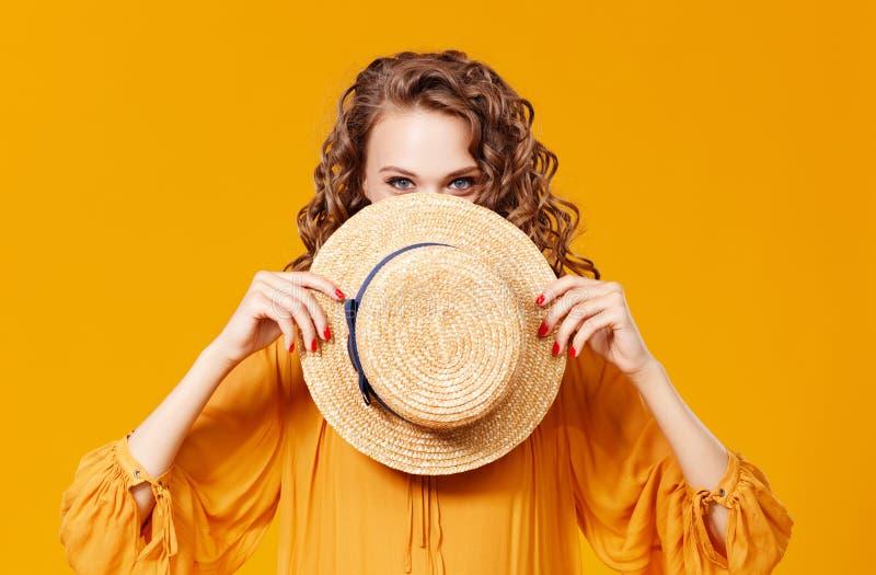 Mujer rizada joven hermosa en sombrero del verano en fondo amarillo imagen de archivo