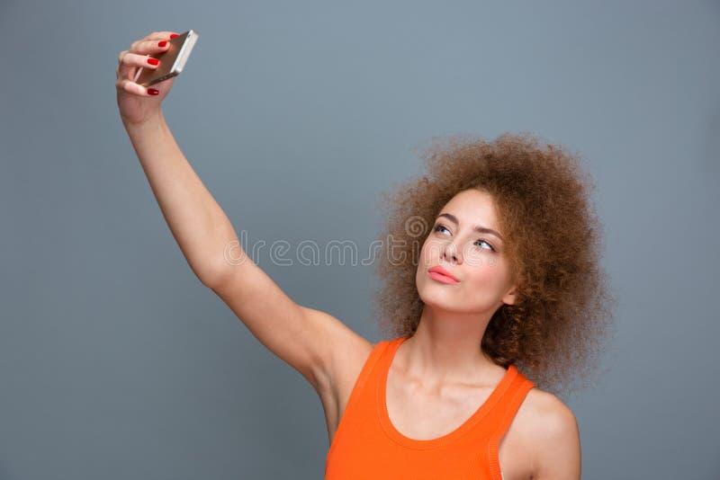 Mujer rizada joven hermosa que hace el selfie usando el teléfono móvil fotografía de archivo