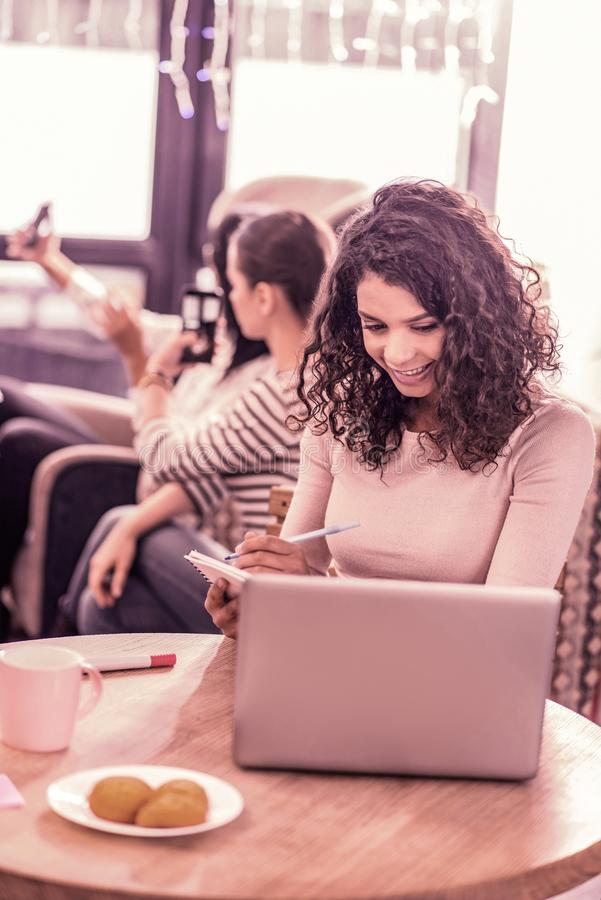 mujer rizada Oscuro-cabelluda que se sienta con su ordenador portátil en panadería mientras que come las galletas sabrosas fotos de archivo