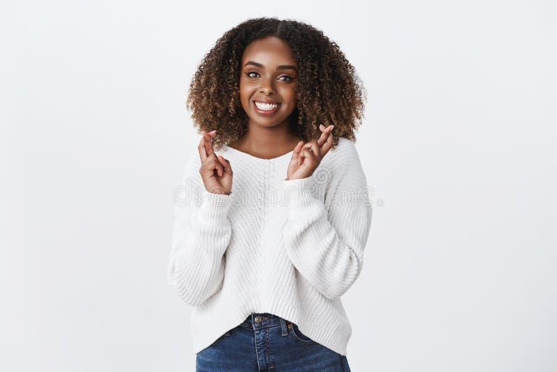 Mujer rizado-cabelluda afroamericana apuesta amistosa encantadora que ruega para la sonrisa de los fingeres de la cruz de la buen foto de archivo