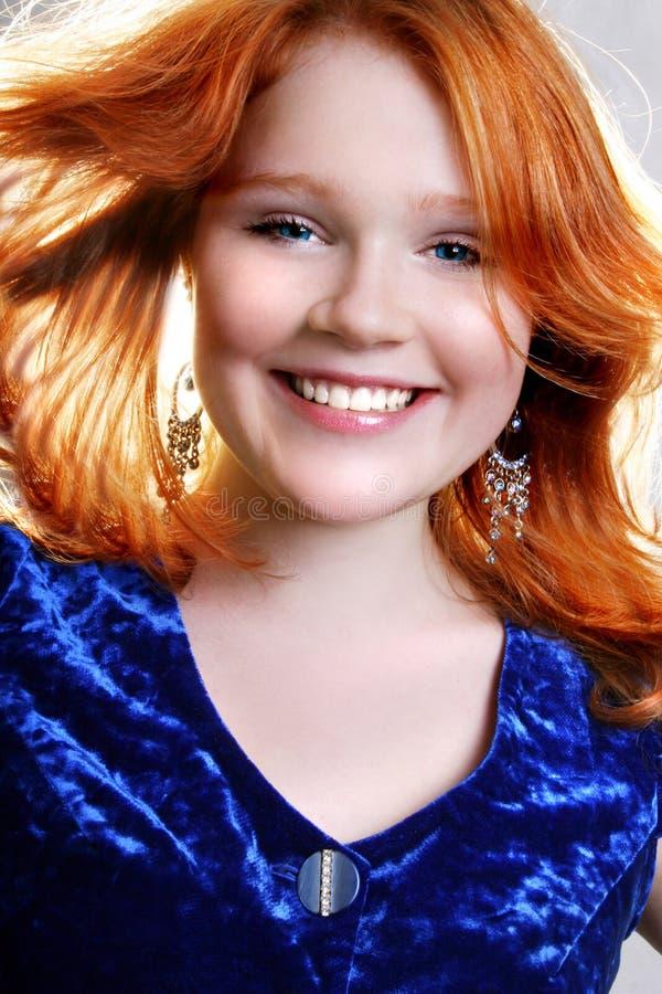Mujer roja atractiva hermosa joven en alineada azul imagenes de archivo