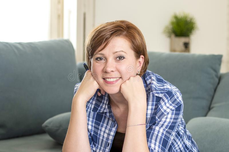 Mujer roja atractiva y feliz joven del pelo alrededor 30 años en casa de la sala de estar de la pluma de tenencia confiada sonrie fotos de archivo libres de regalías