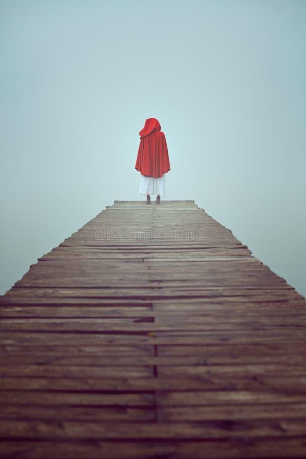 Mujer roja de la capilla en un embarcadero brumoso imagen de archivo