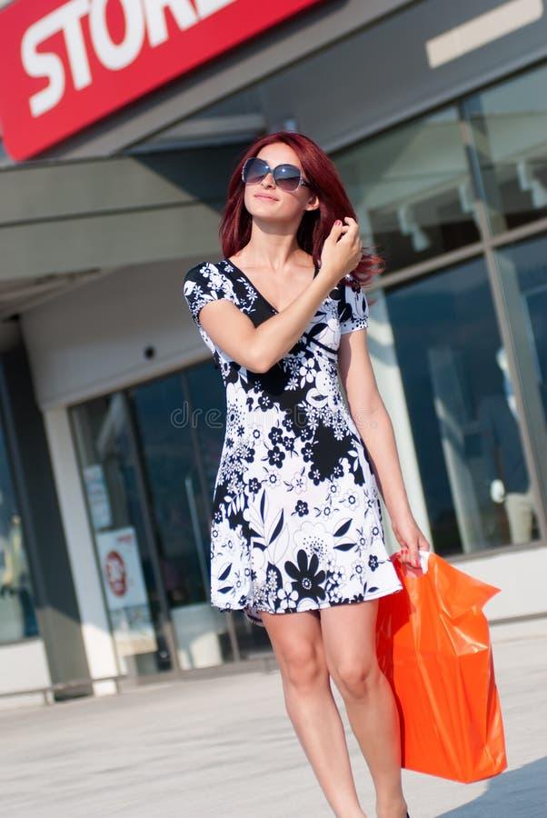 Mujer roja del pelo con el panier contra de la entrada de la tienda imagen de archivo libre de regalías