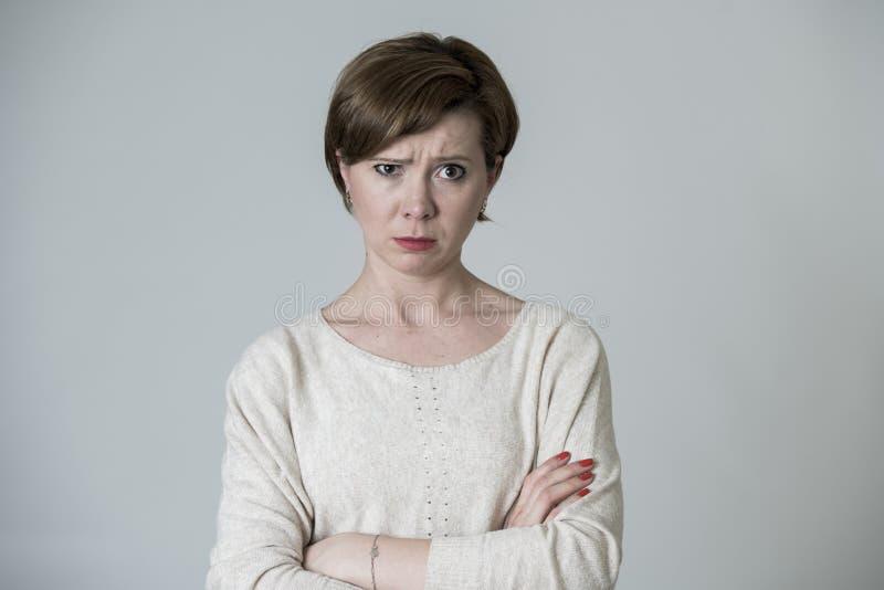 Mujer roja enojada y trastornada enojada joven del pelo que plantea la mirada triste y cambiante a la cámara aislada en fondo gri fotografía de archivo libre de regalías