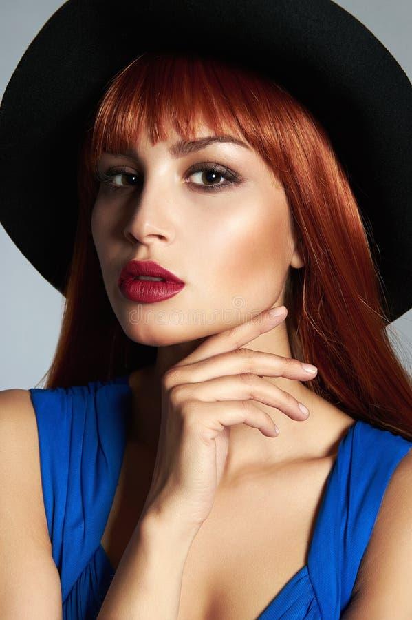 Mujer roja hermosa del pelo en sombrero imagen de archivo