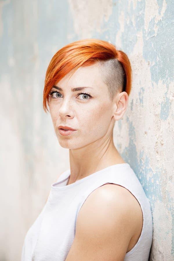 Mujer roja joven del pelo por la pared vieja foto de archivo libre de regalías