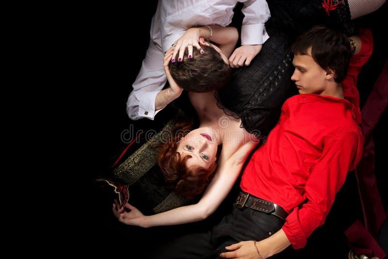 Mujer roja y dos hombres - estilo de la decadencia foto de archivo