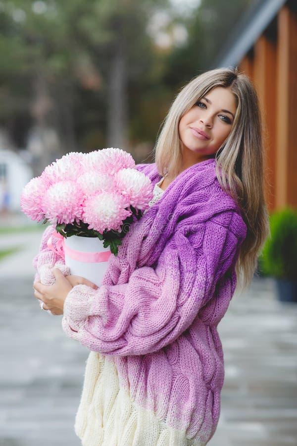 Mujer romántica con las flores en sus manos imagen de archivo
