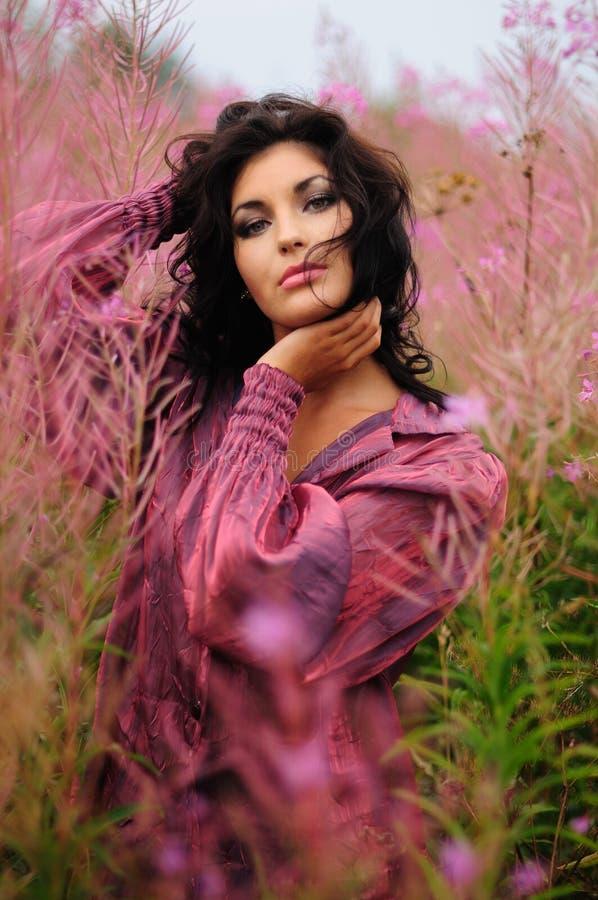 Mujer romántica entre las flores rosadas imagenes de archivo