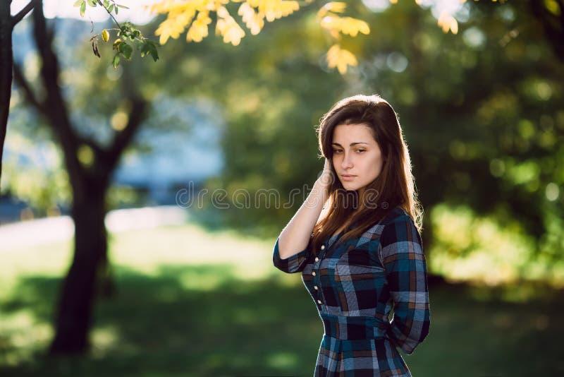 Mujer romántica joven en vestido azul a cuadros largo sobre el retrato del otoño del fondo Muchacha bonita que presenta en parque fotografía de archivo