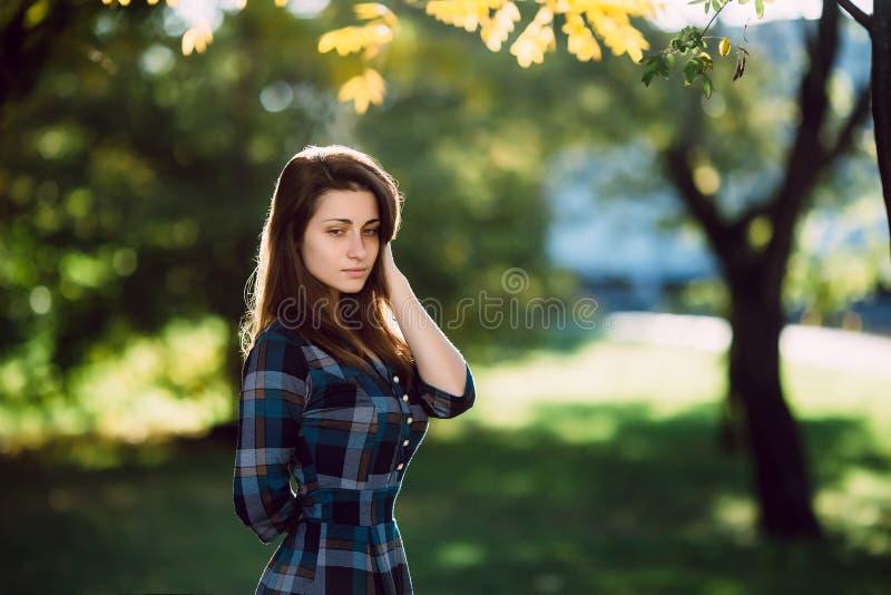 Mujer romántica joven en vestido azul a cuadros largo sobre el retrato del otoño del fondo Muchacha bonita que presenta en parque imagenes de archivo