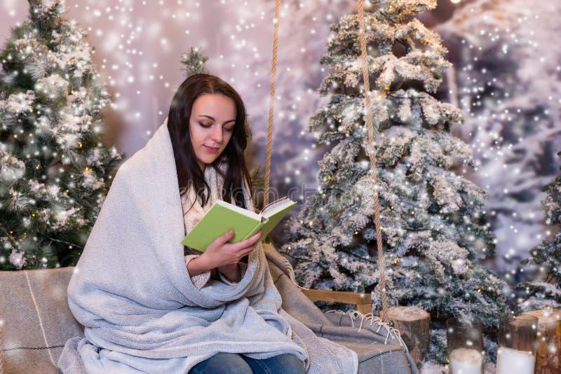 Mujer romántica que lee un libro mientras que se sienta en un oscilación y un wrapp imagenes de archivo