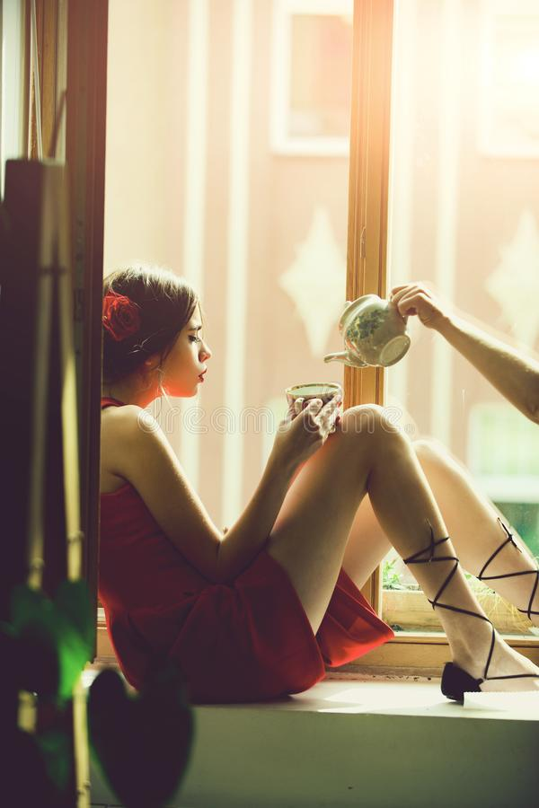 Mujer romántica que piensa en futuro mujer en té de consumición del vestido rojo de la taza fotografía de archivo