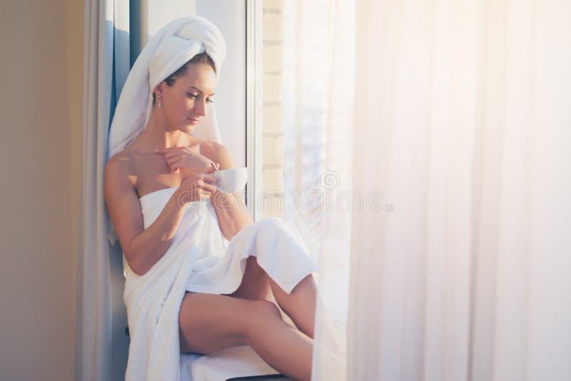 Mujer romántica que se sienta antes de ventana y que admira salida del sol o puesta del sol con la toalla en su cuerpo principal  imagenes de archivo