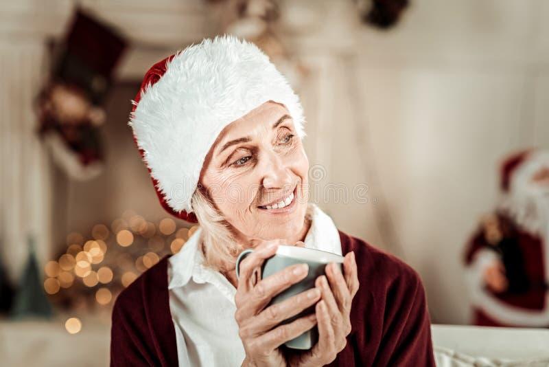 Mujer romántica satisfecha que mira a un lado y que sostiene una taza fotografía de archivo libre de regalías