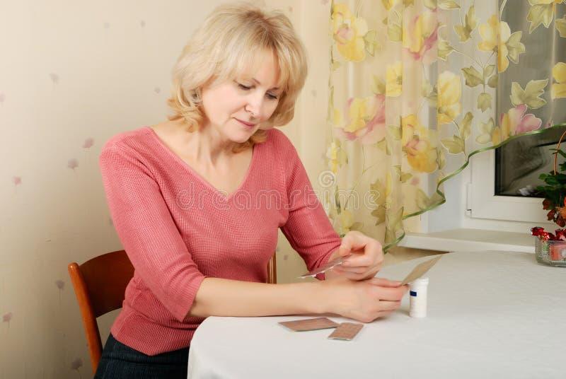 Mujer rubia adulta con las píldoras imagenes de archivo