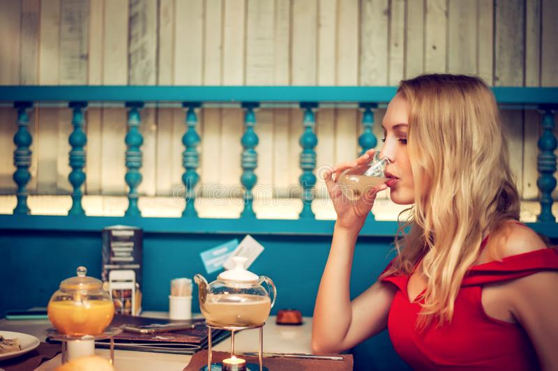 Mujer rubia adulta joven hermosa que bebe té amarillo de la fruta imagen de archivo