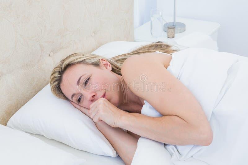 Mujer rubia agotada que llora en cama imagen de archivo libre de regalías