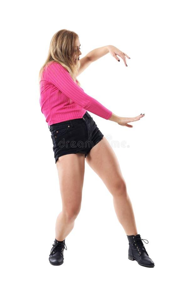 Mujer rubia agraciada en rosa un baile de la blusa con mangas Vista lateral foto de archivo