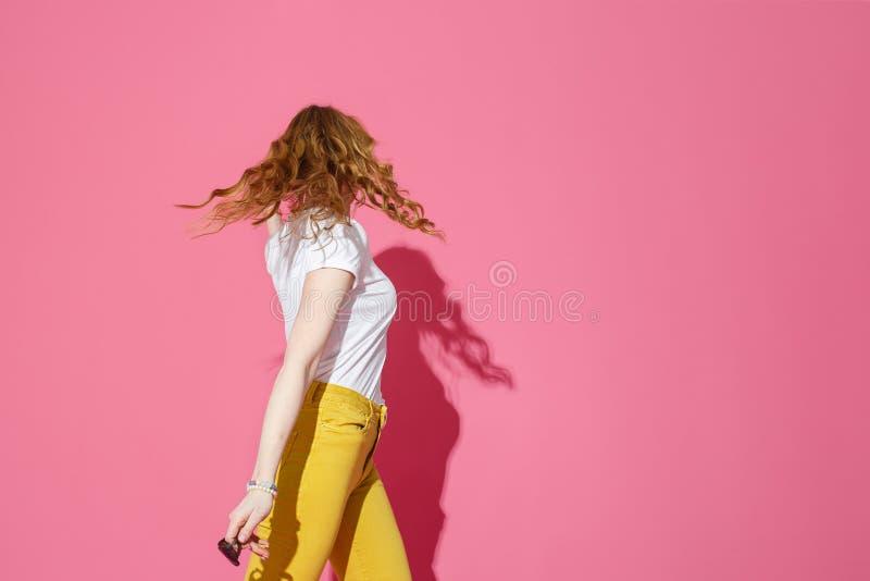 Mujer rubia alegre en la camiseta blanca y el baile amarillo de moda de los vaqueros en fondo rosado imagen de archivo