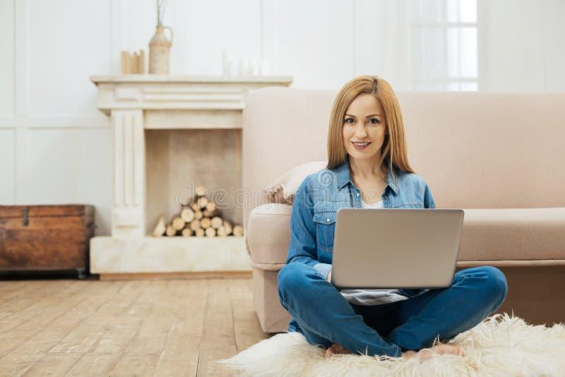 Mujer rubia alegre que trabaja en el ordenador portátil fotografía de archivo libre de regalías