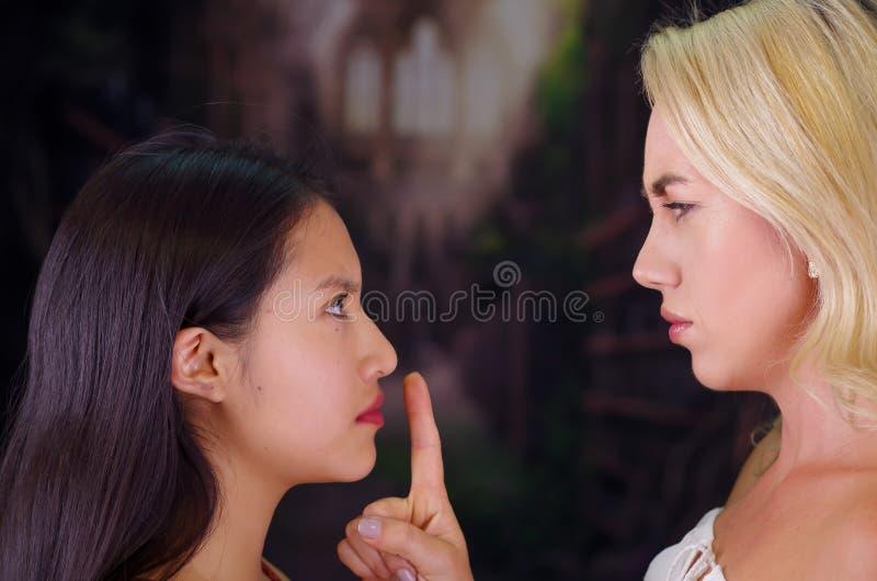 Mujer rubia americana enojada joven, poniendo su finger en la boca de una mujer extranjera, fingiendo mantenerla silencio imágenes de archivo libres de regalías