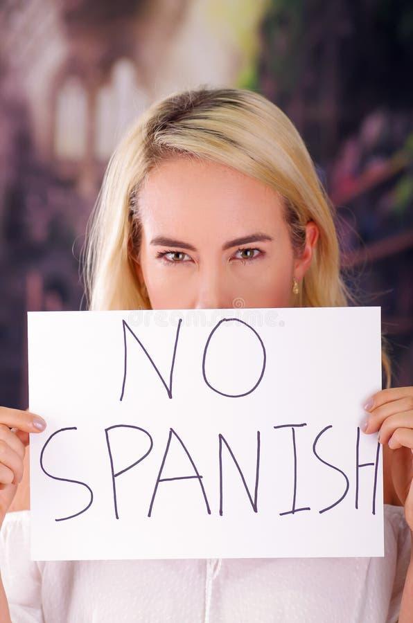 Mujer rubia americana enojada joven que lleva a cabo un trozo de papel con una descripción de no español, del racismo, violencia  foto de archivo libre de regalías