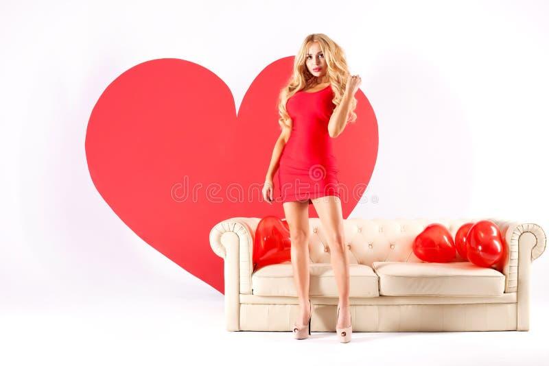 Mujer rubia atractiva con el corazón grande imagenes de archivo