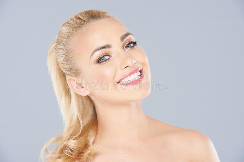 Mujer rubia atractiva con una sonrisa de emisión imagen de archivo