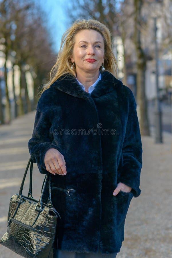 Mujer rubia atractiva elegante en un abrigo de invierno caliente imagen de archivo libre de regalías