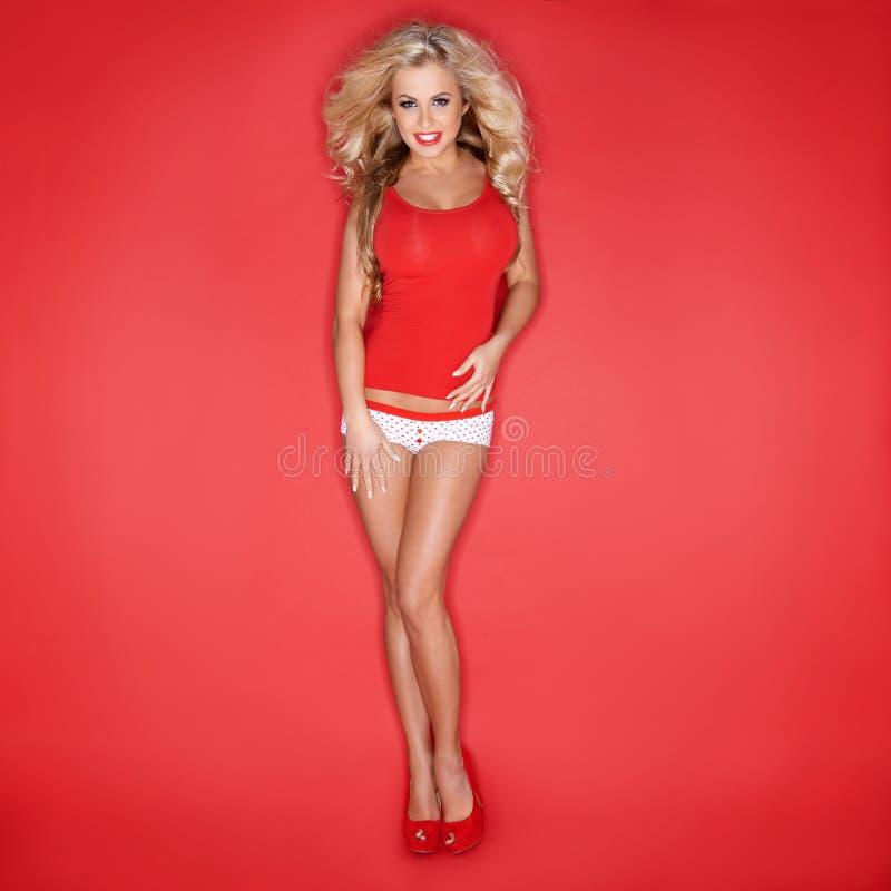 Mujer rubia atractiva en camisetas sin mangas rojas imagen de archivo libre de regalías