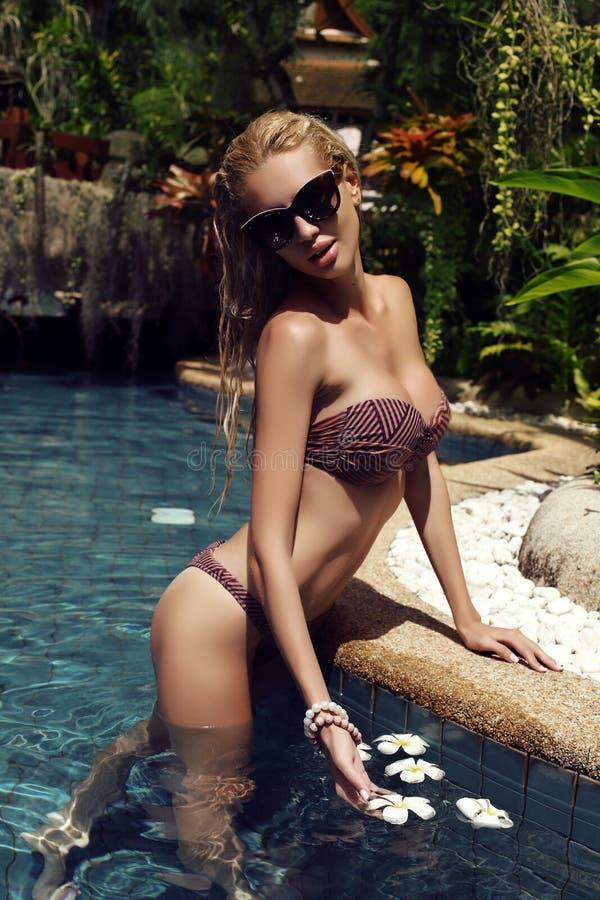 Mujer rubia atractiva en el bikini elegante que presenta en piscina fotografía de archivo libre de regalías