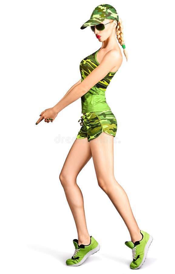 Mujer rubia atractiva en el estilo del camuflaje que hace el arma imagen de archivo libre de regalías