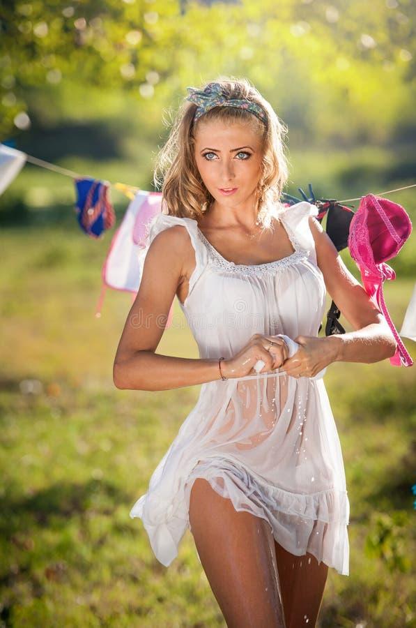 Mujer rubia atractiva en el vestido mojado del cortocircuito del blanco que pone la ropa para secarse en sol Hembra joven del pel fotos de archivo libres de regalías