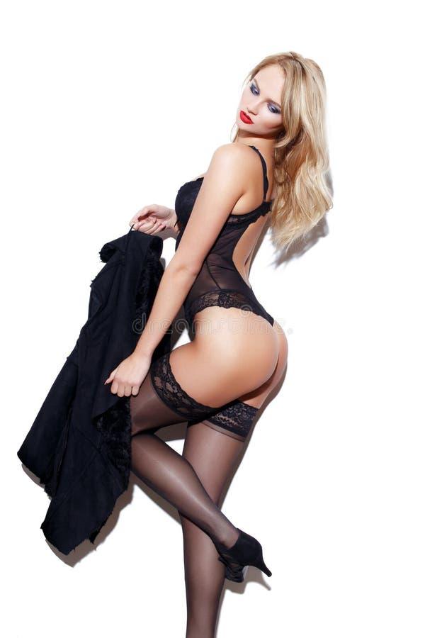 Mujer rubia atractiva en la ropa interior que presenta en la pared blanca imagen de archivo libre de regalías