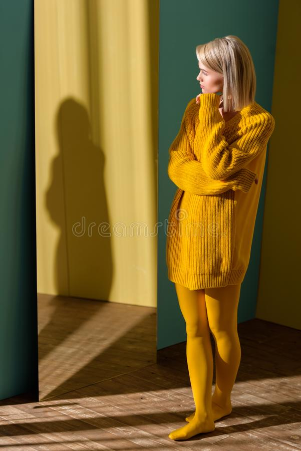 mujer rubia atractiva en la situación amarilla del suéter y de las medias imágenes de archivo libres de regalías
