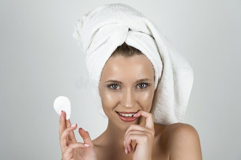 Mujer rubia atractiva en la toalla blanca en su cabeza que sostiene el cojín de algodón en una mano y que toca su diente con su f fotos de archivo