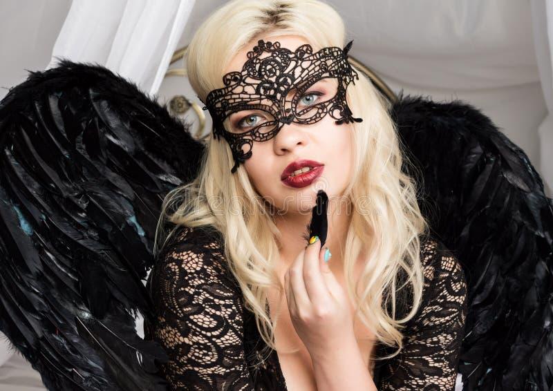 Mujer rubia atractiva en una máscara del cordón que sostiene una pluma negra cerca de su cara imagen de archivo