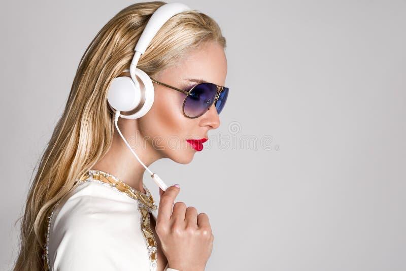 Mujer rubia atractiva hermosa con el pelo largo y cuerpo perfecto en un traje blanco elegante que se sienta con los auriculares imágenes de archivo libres de regalías