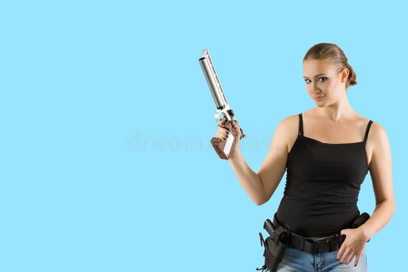 Mujer rubia atractiva hermosa joven que sostiene la arma de mano disponible imagenes de archivo