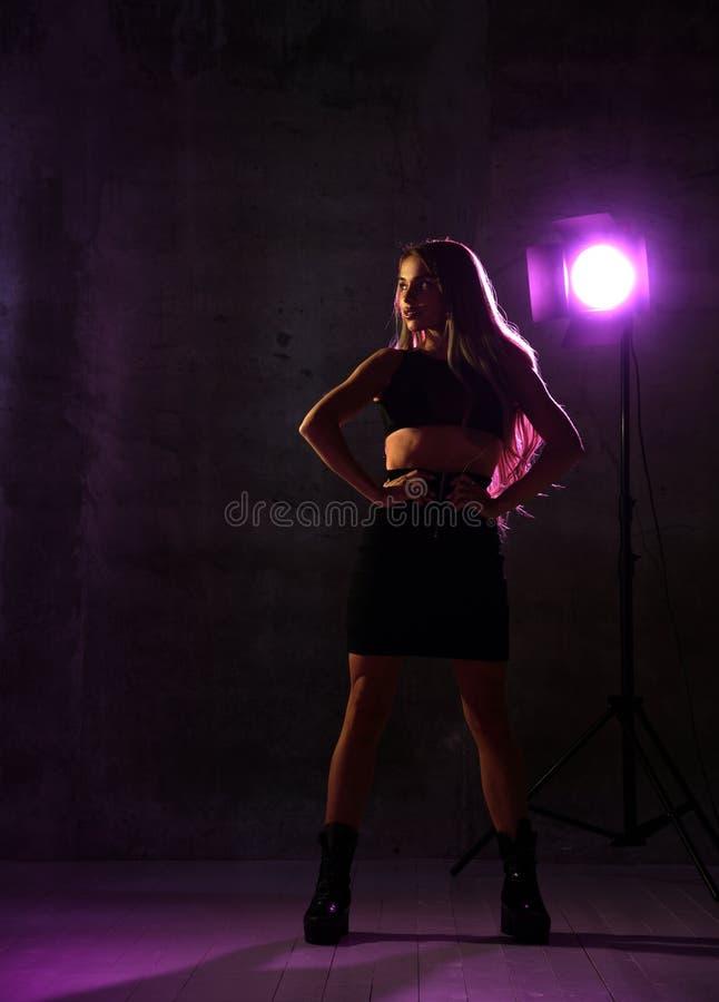Mujer rubia atractiva hermosa que presenta en luz de neón azul y rosada en sujetador del cuero de la moda foto de archivo